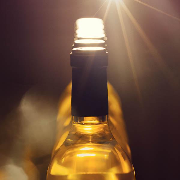 Plusieurs bouteilles de vin alignées avec un rayon lumineux.
