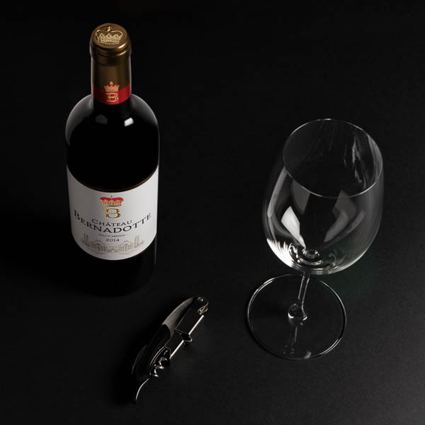 Bouteille de vin, verre vide et limonadier sur un fond noir.