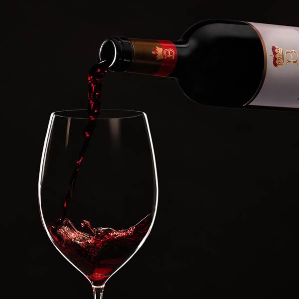 Vin rouge en train de couler d'une bouteille dans un verre.