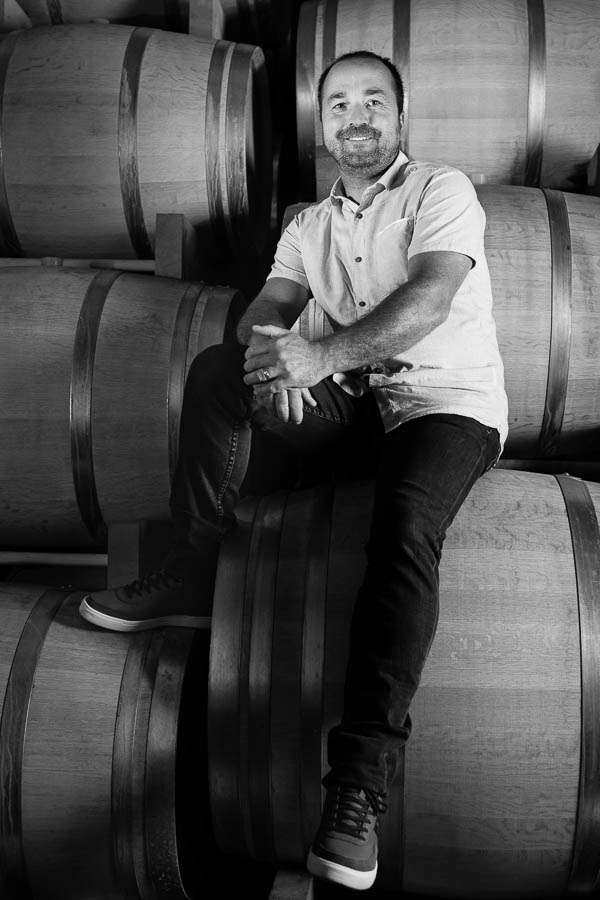 Portrait d'un vigneron assis sur des barriques.