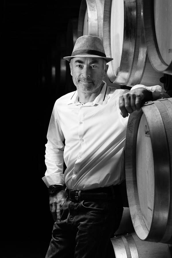 Portrait en noir et blanc d'un vigneron s'appuyant sur des barriques.