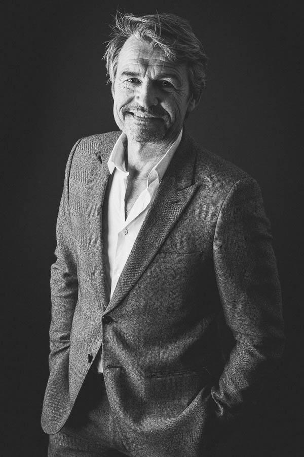 Portrait d'un homme en costume en studio. Photo en noir et blanc.